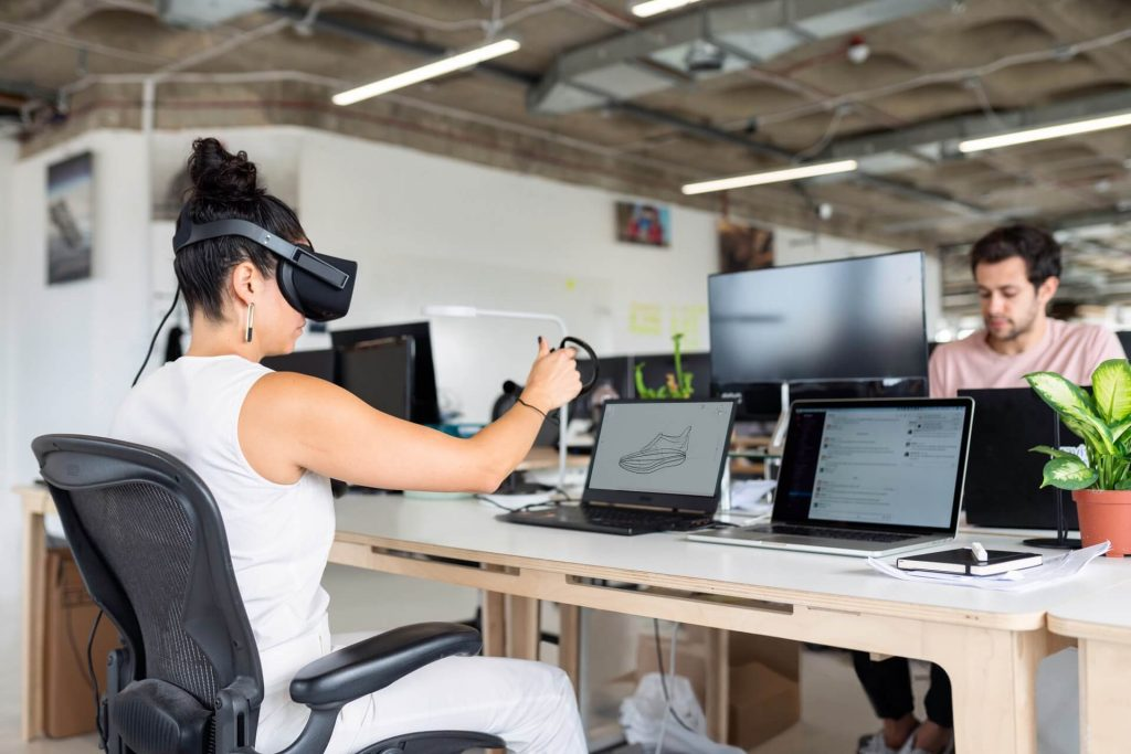 A woman in white tank top using black laptop computer with vr to improve customer experience
