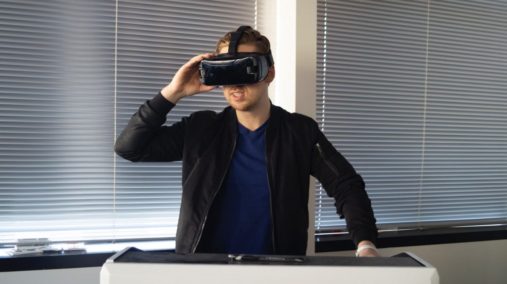 A man holding a VR headset while watching a virtual reality experience