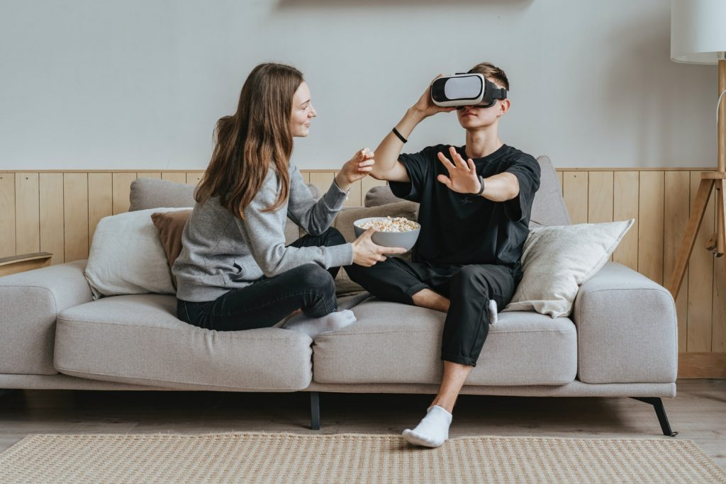 Man and a woman on a sofa using a VR headset